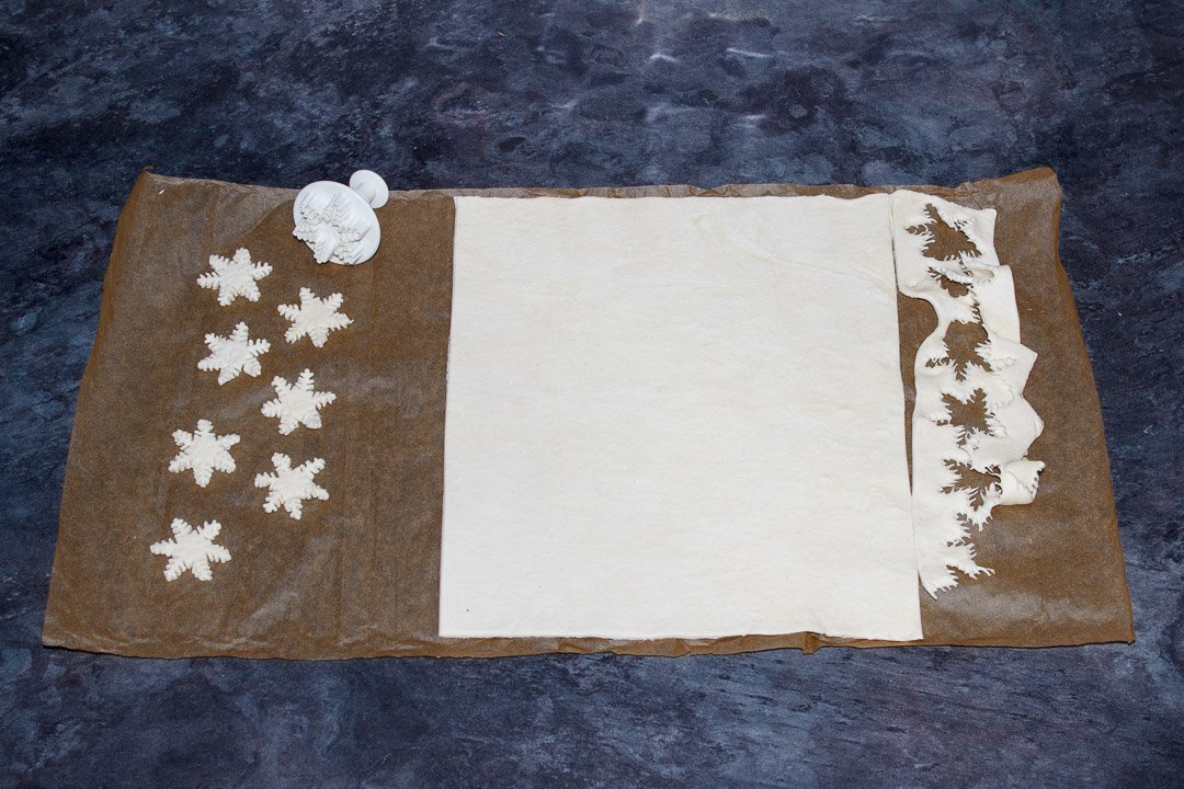 Snowflakes being cut out of puff pastry with a plunge cutter