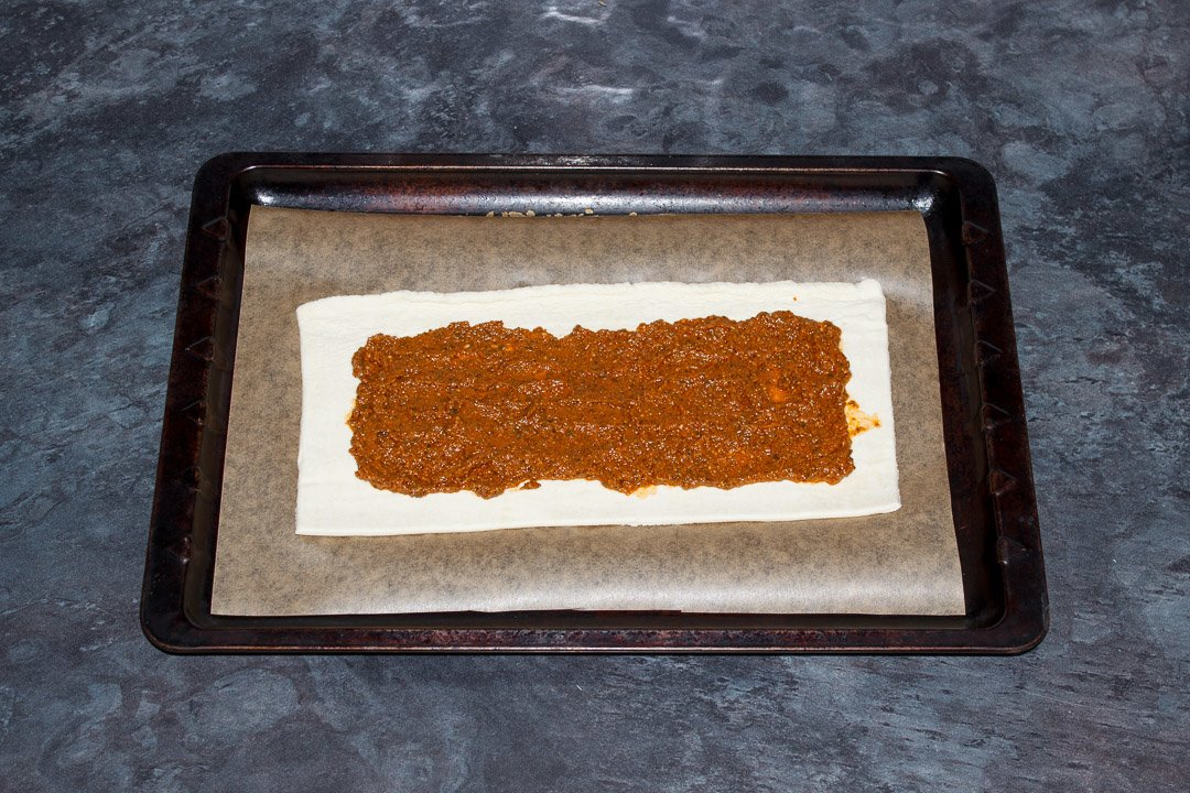 A rectangle of puff pastry on a lined baking tray topped with red pesto