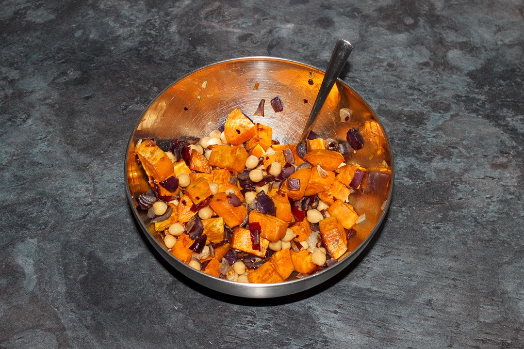 Chickpeas, roasted sweet potatoes, red onion and garlic mixed together in a metal bowl