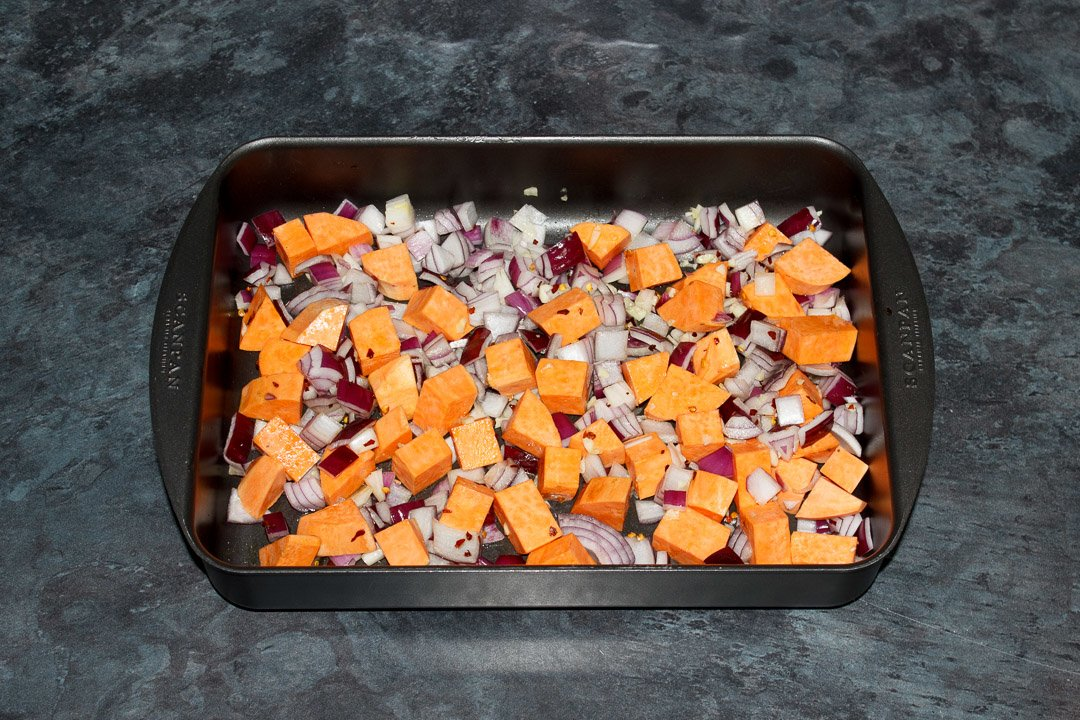 Sweet potato. red onion and garlic coated in oil and salt in a roasting tray