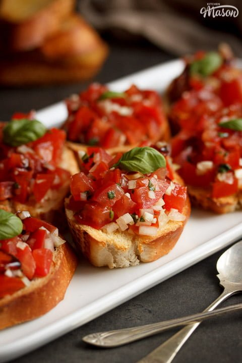 bruschetta topped with a basil leaf on a white serving plate