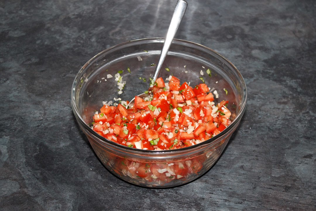 Bruschetta topping in a large bowl with a spoon