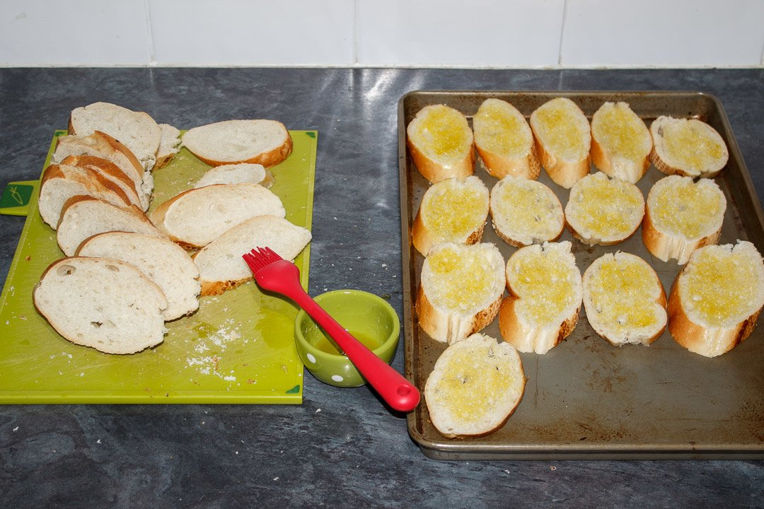 Slices of baguette being brushed on both sides with olive oil then placed onto a baking sheet