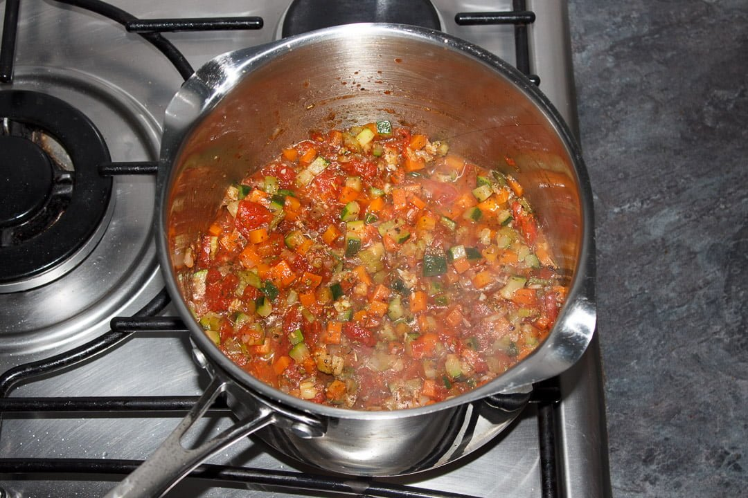 Vegetables, tinned tomatoes and herbs cooking in a large saucepan