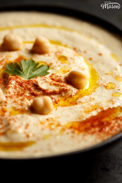 Homemade hummus in a bowl topped with chickpeas, olive oil, paprika and parsley