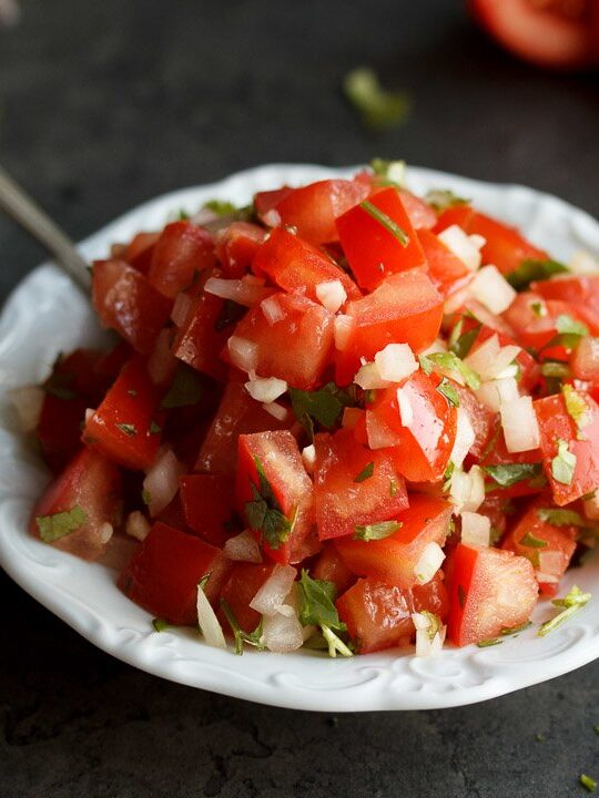 Fresh tomato salsa in a white bowl with a spoon