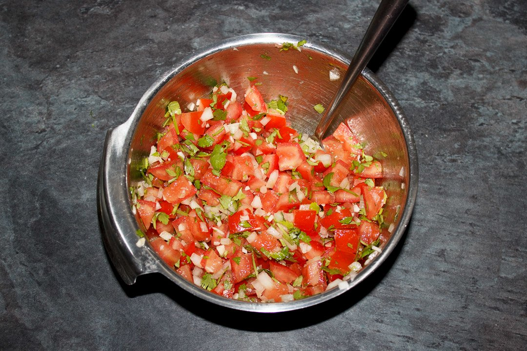 Diced desseded tomato, diced onion, garlic and coriander mixed together in a silver bowl