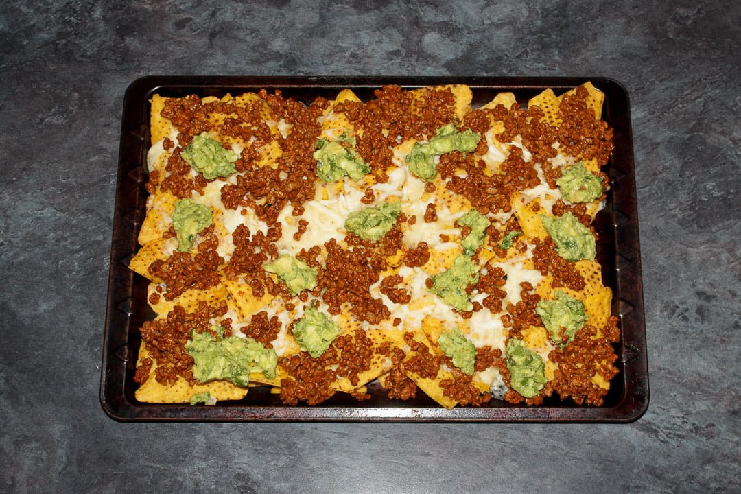 Tortilla chips spread out on a baking tray covered in melted cheese, taco seasoned soya mince and guacamole