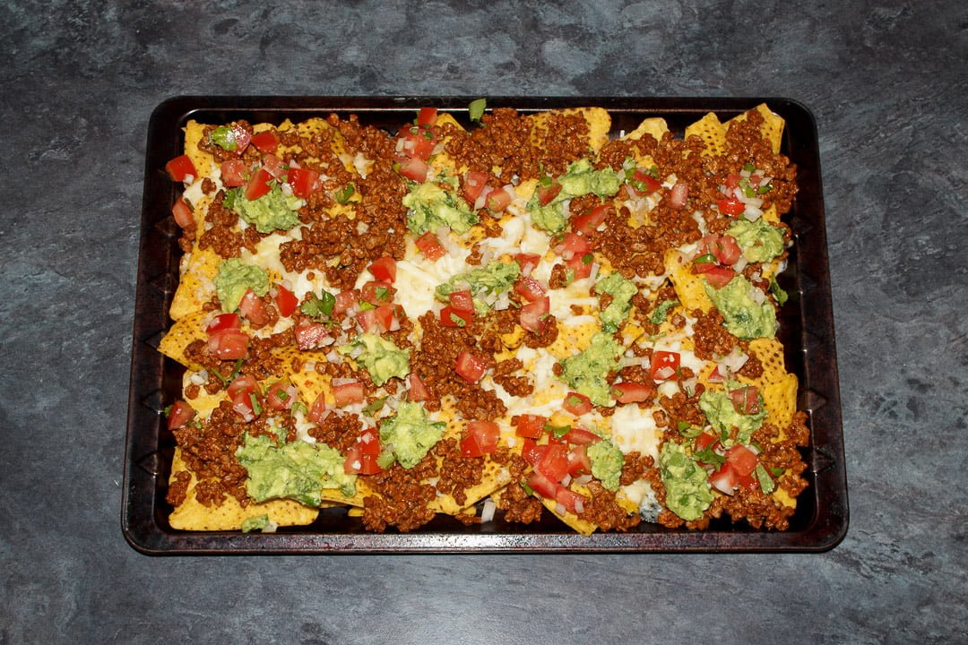 Tortilla chips spread out on a baking tray covered in melted cheese, taco seasoned soya mince, guacamole and tomato salsa