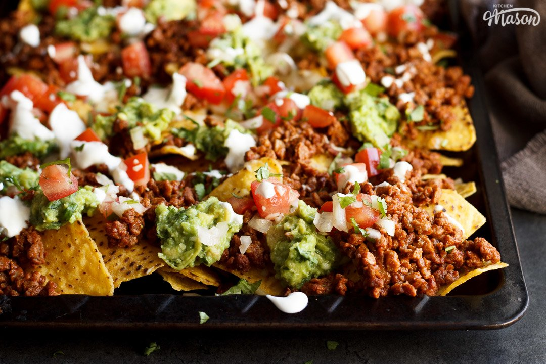 Loaded homemade nachos on a baking tray