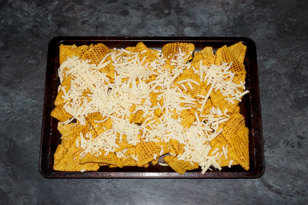 Tortilla chips spread out on a baking tray covered in grated cheese
