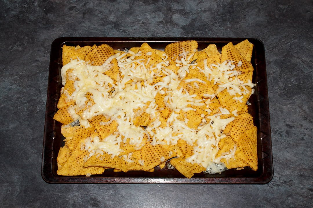 Tortilla chips spread out on a baking tray covered in melted cheese