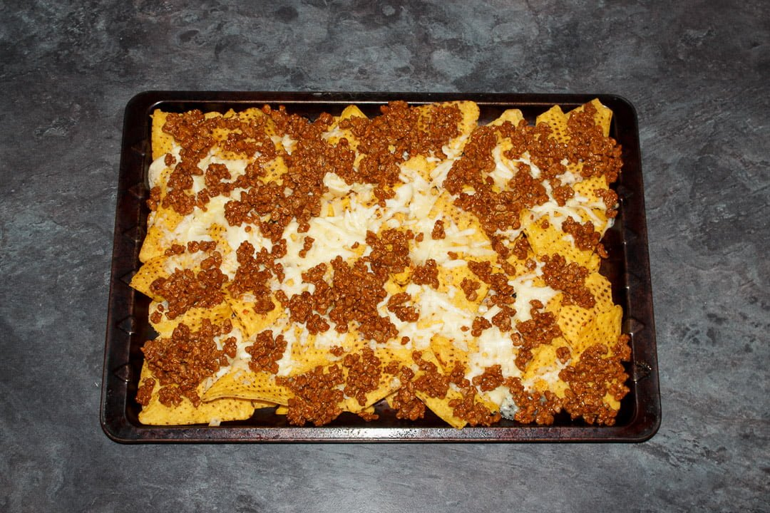Tortilla chips spread out on a baking tray covered in melted cheese and taco seasoned soya mince