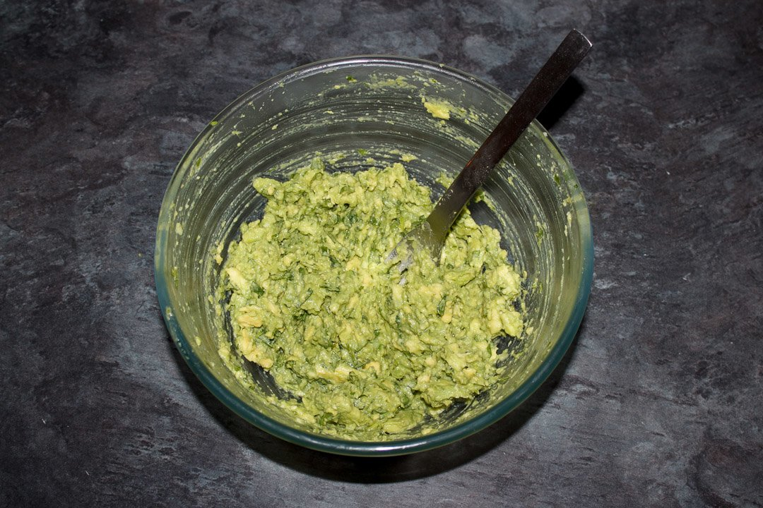 Guacamole in a glass bowl with a fork