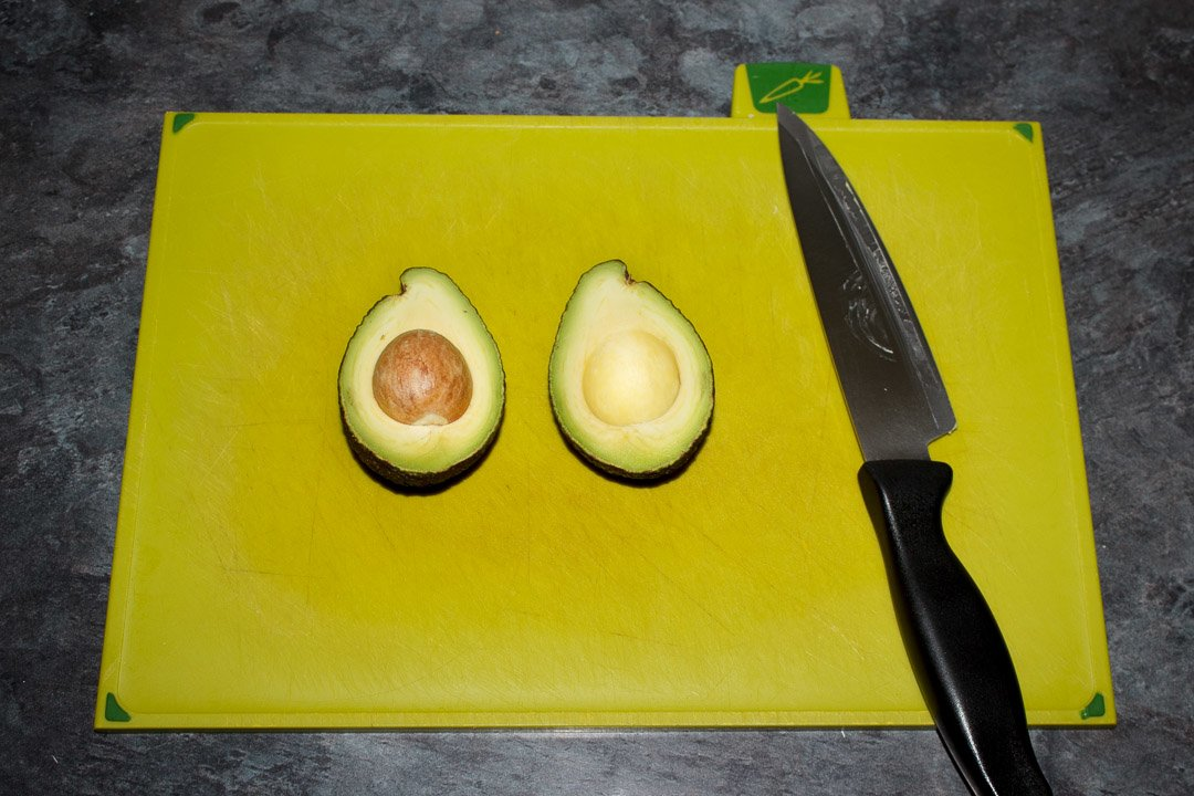 a halved avocado on a chopping board with a sharp knife