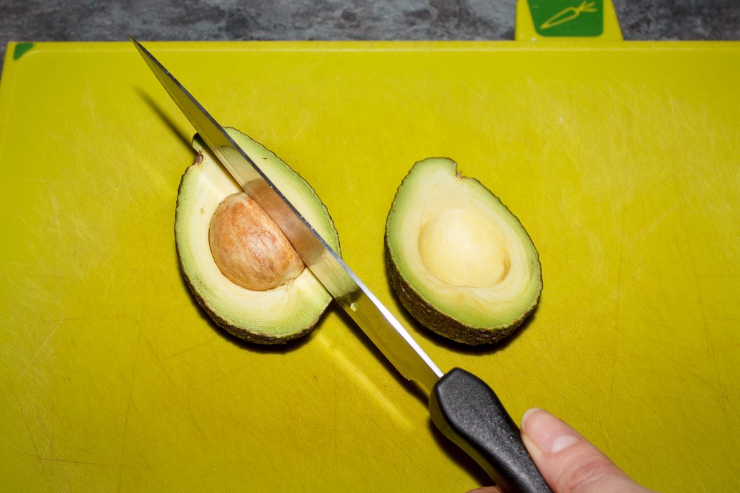 a knife cutting into an avocado stone on a green chopping board