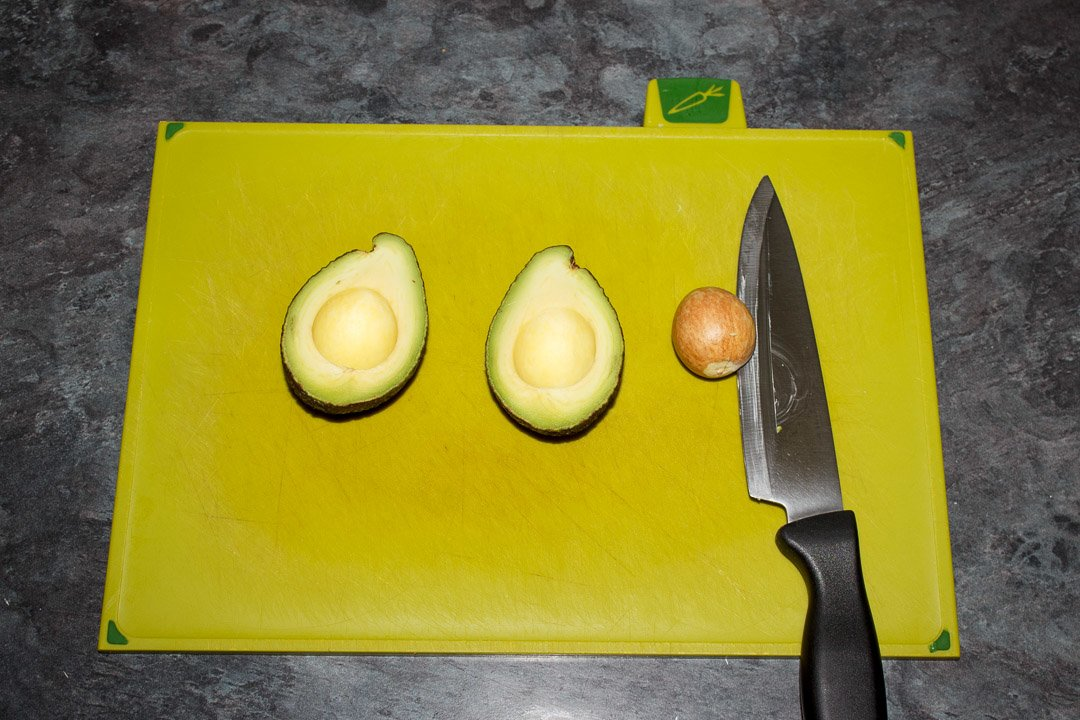 A halved avocado on a green chopping board with a knife and the avocado pip