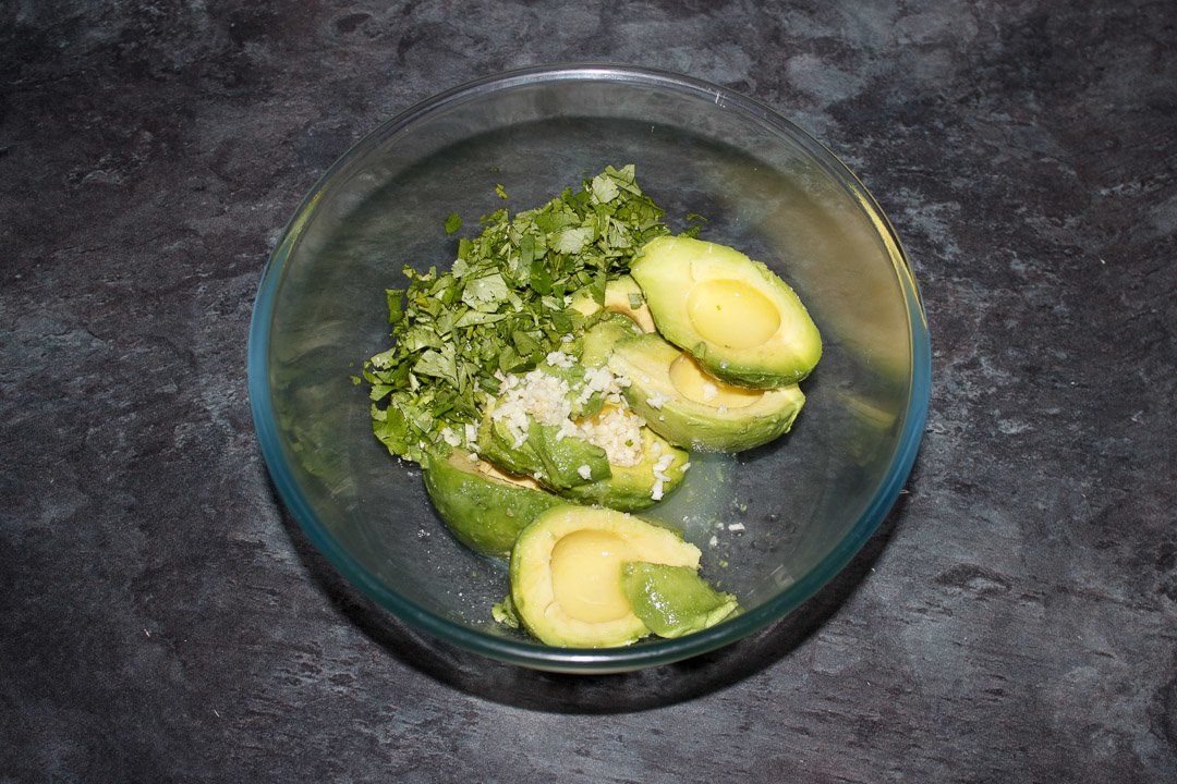 Guacamole ingredients in a glass bowl
