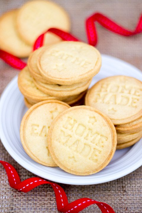 Butter biscuits piled up on a white plate with red ribbon curled around it