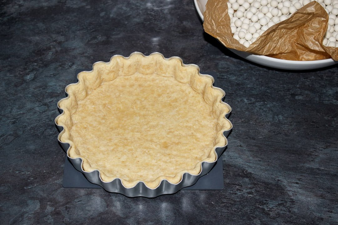 A blind baked shortcrust pastry case in a tart tin with the baking beans removed