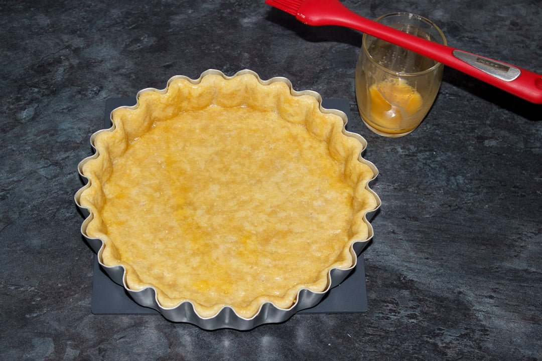 A blind baked shortcrust pastry case in a tart tin with the baking beans removed and beaten egg brushed over it