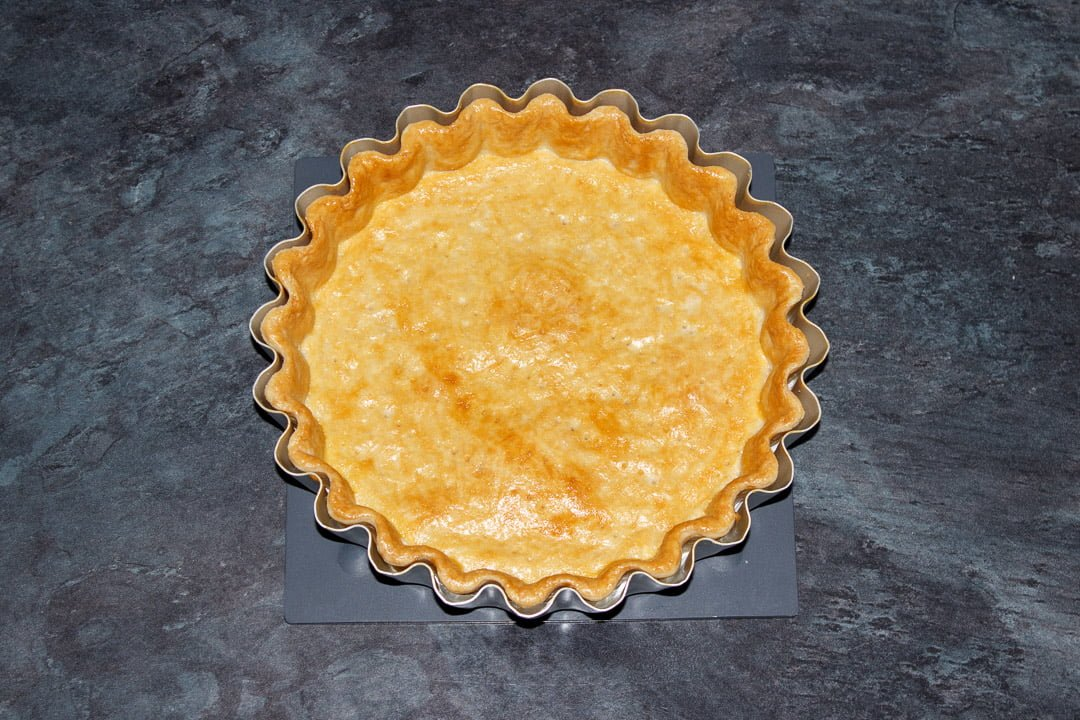 A baked shortcrust pastry case in a tart tin