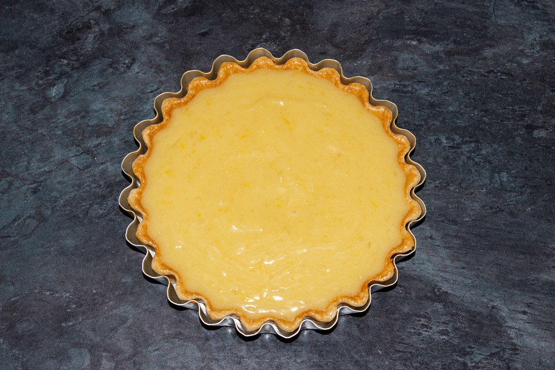 A shortcrust pastry case in a tart tin filled with a lemon curd filling