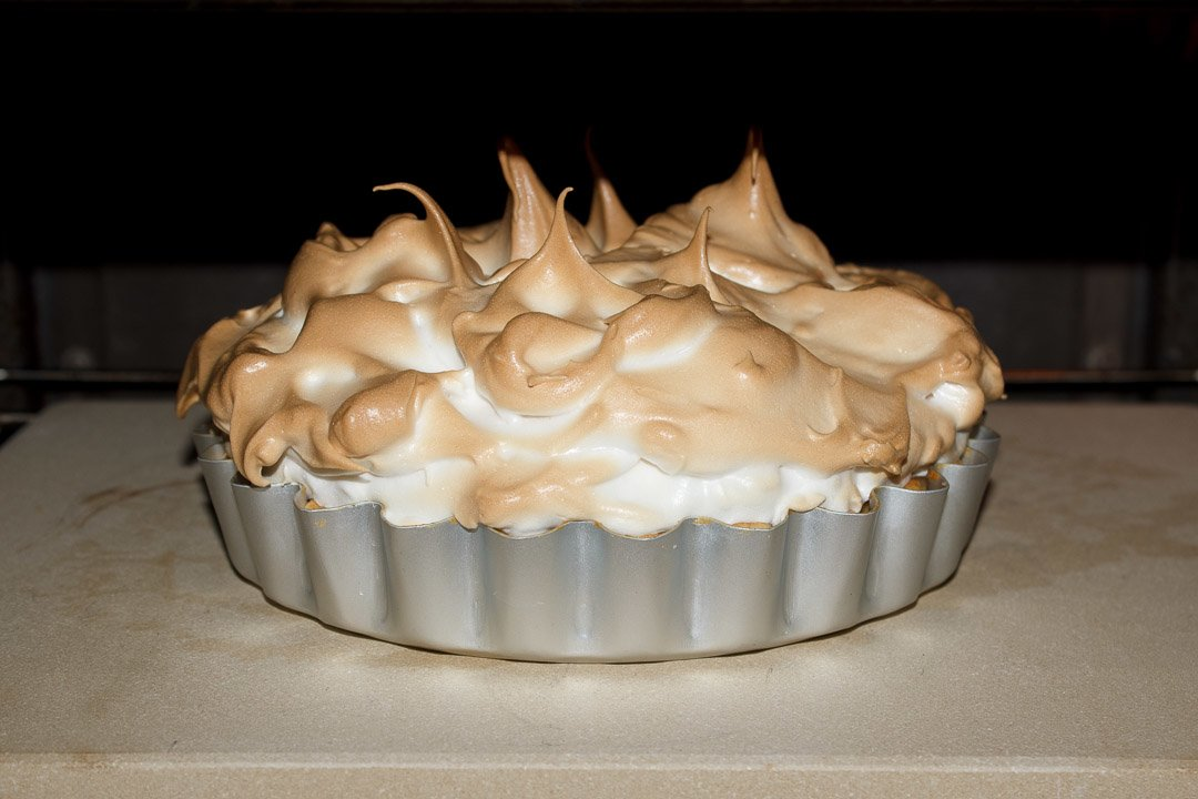 Part baked meringue on top of a lemon meringue pie, in the oven