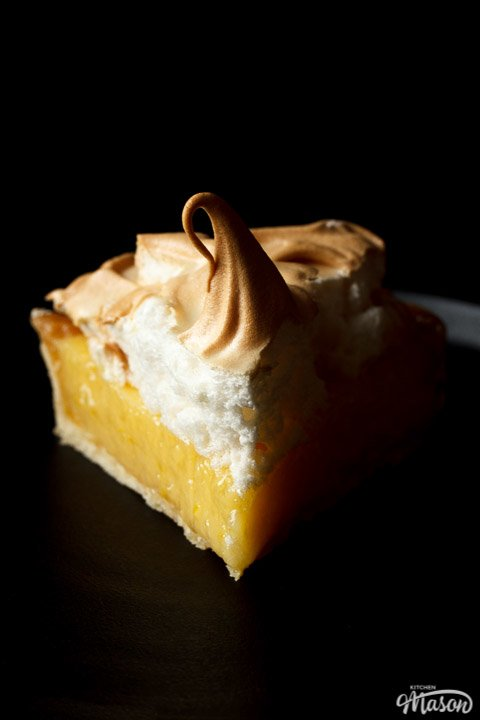 A lemon meringue pie slice on a black plate with a fork