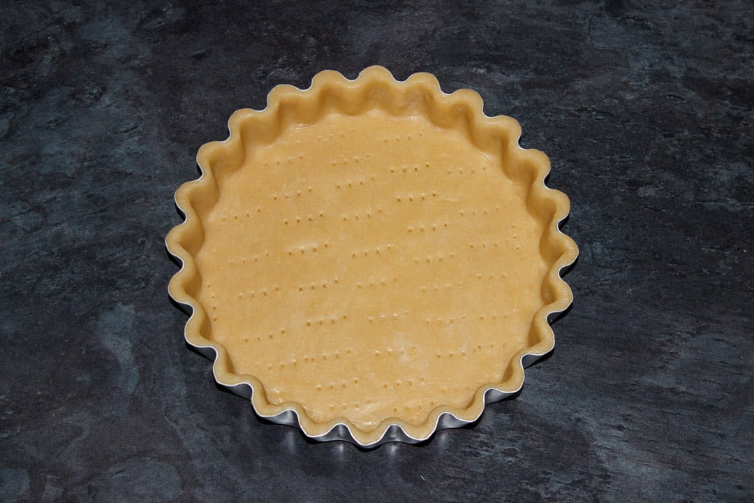A tart tin lined with shortcrust pastry that's been pricked with a fork