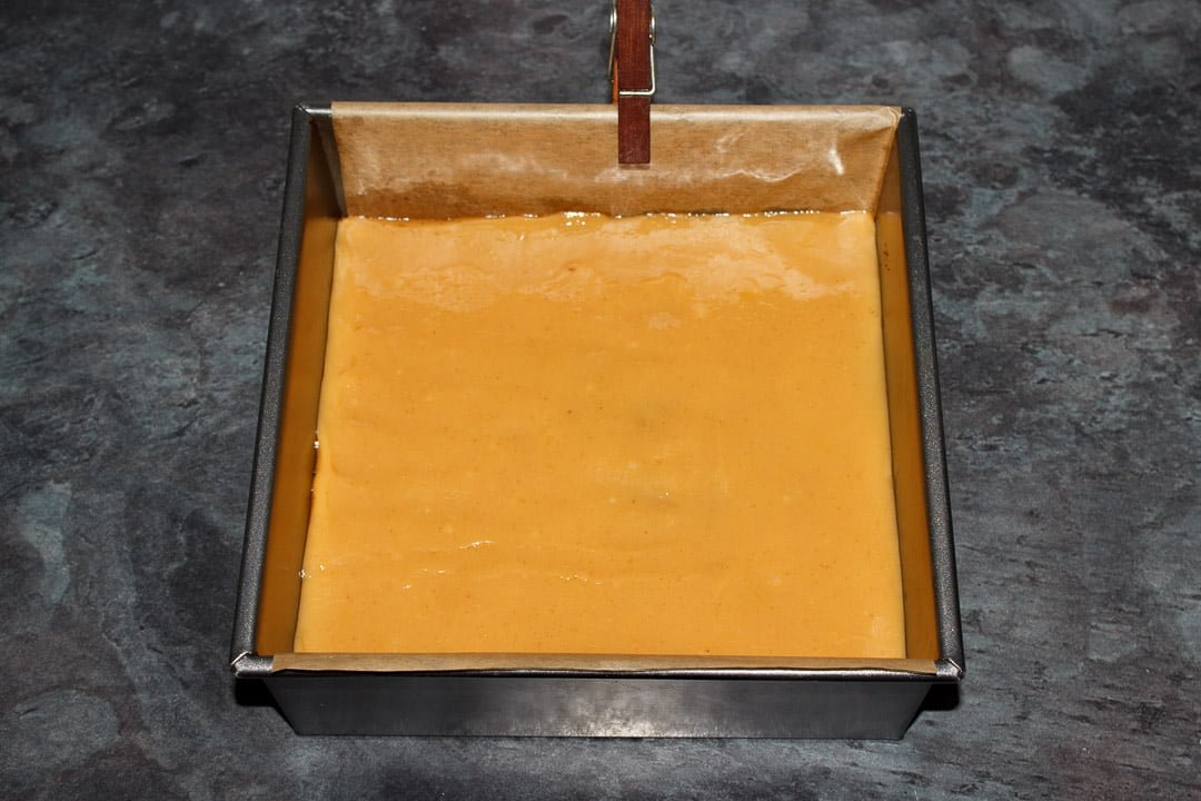 A caramel layer on top of brownie in a lined square baking tin