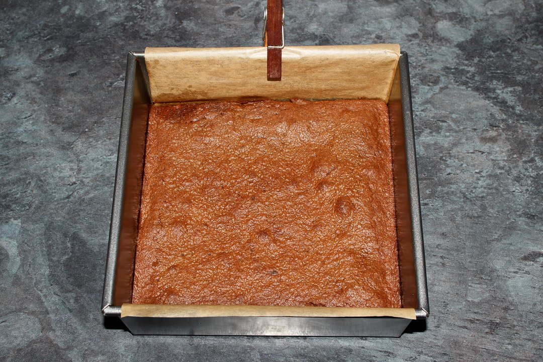 Cooked brownie in a lined square baking tin