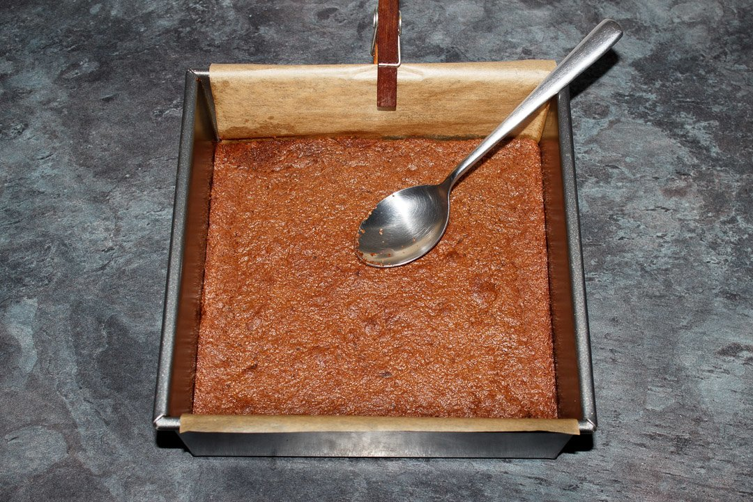 Cooked brownie in a lined square baking tin being levelled off with a metal spoon