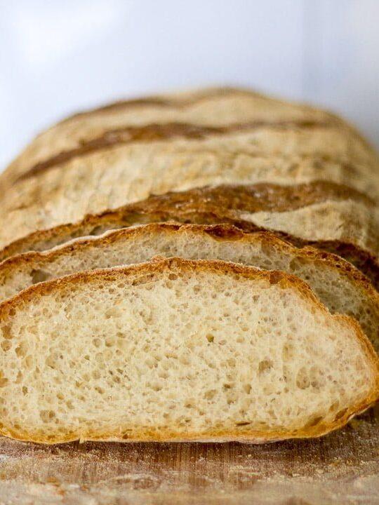 No knead mug bread sliced on a wooden chopping board