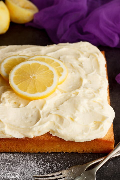 A lemon traybake cake on a worktop topped with lemon slices for decoration