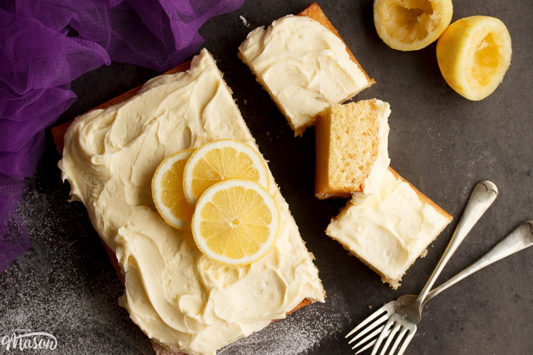 Lemon traybake part sliced on a worktop with slices of lemon on top