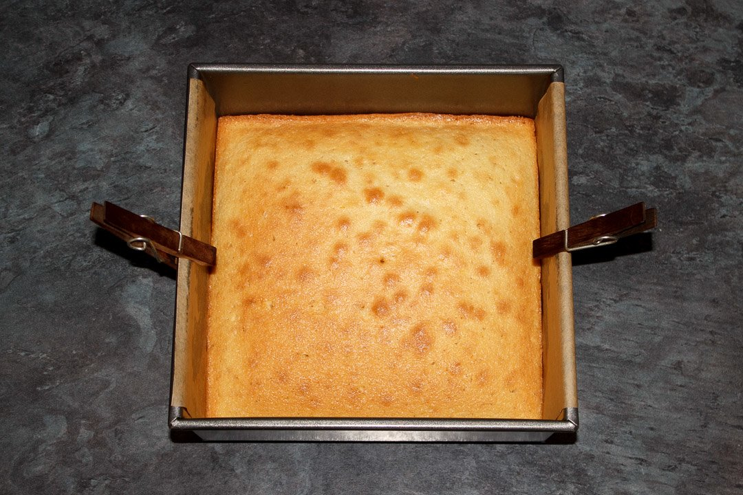A baked lemon traybake cake cooling in a square tin