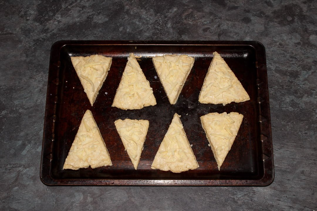 Cheese scones on a baking tray brushed with milk and topped with cheese