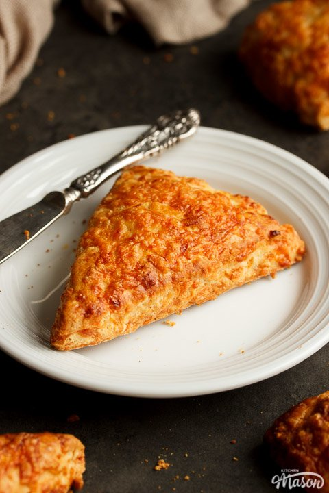 A cheese scone on a white plate with a knife surrounded by a cloth and more cheese scones
