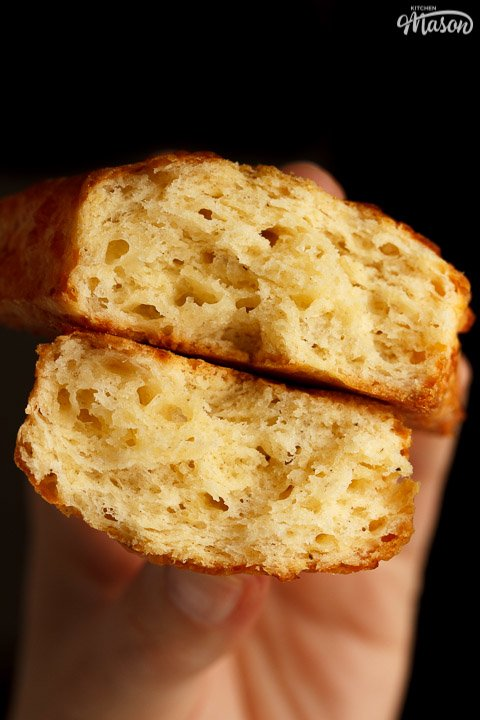 Two halves of a cheese scone being held so you can see the light flaky centre