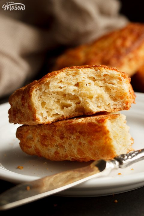 Two halves of a cheese scone on top of each other on a white plate with a knife