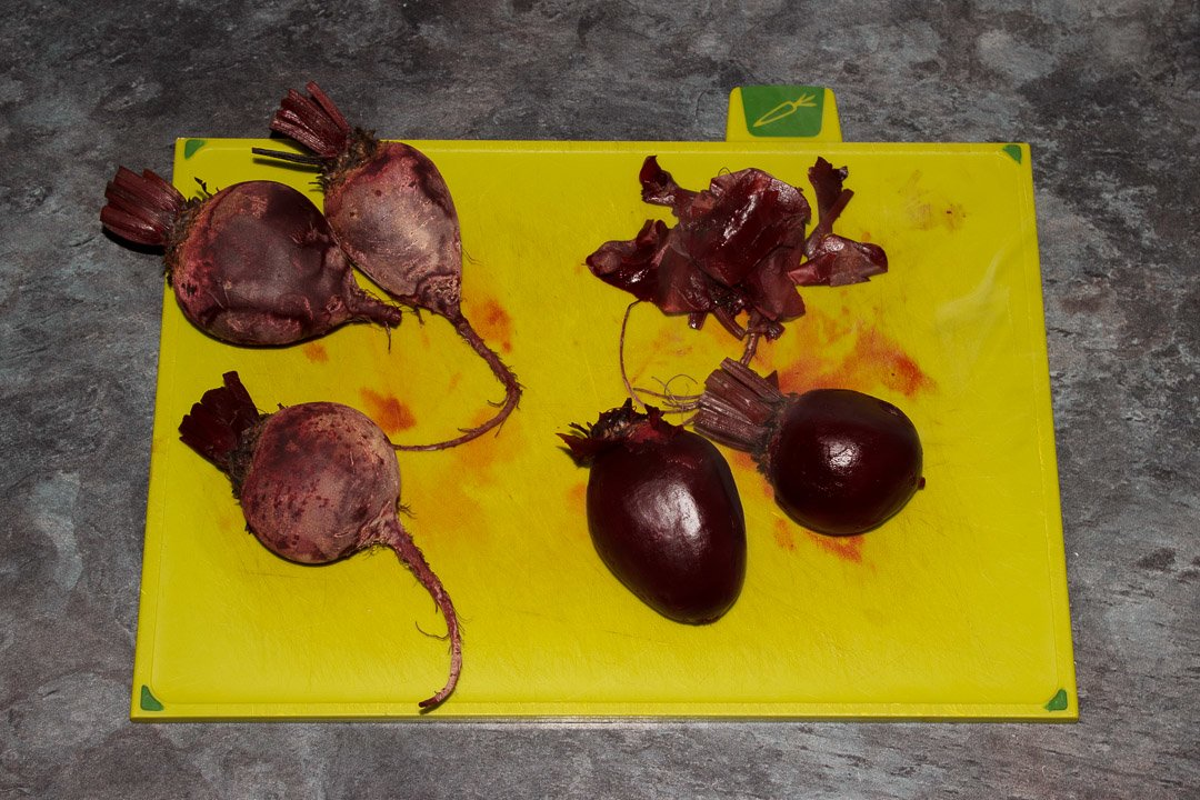 Whole beetroot having their skins peeled off on a chopping board