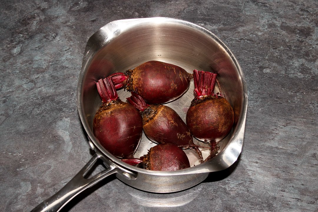 Washed whole beetroot with the stems trimmed in a large saucepan