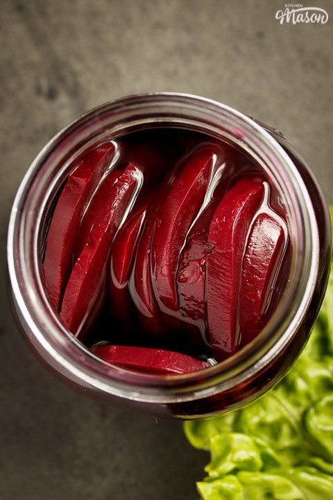 Pickled beetroot in a jar with a lettuce leaf next to it