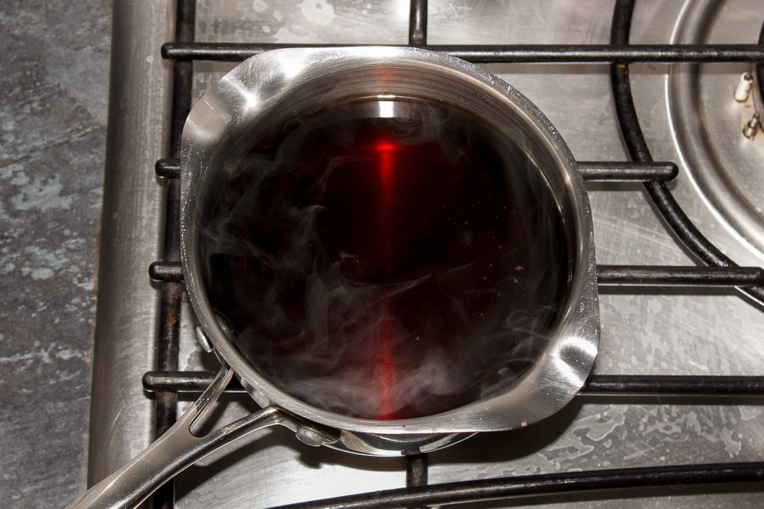 Vinegar and sugar being heated gently in a small pan over a low heat