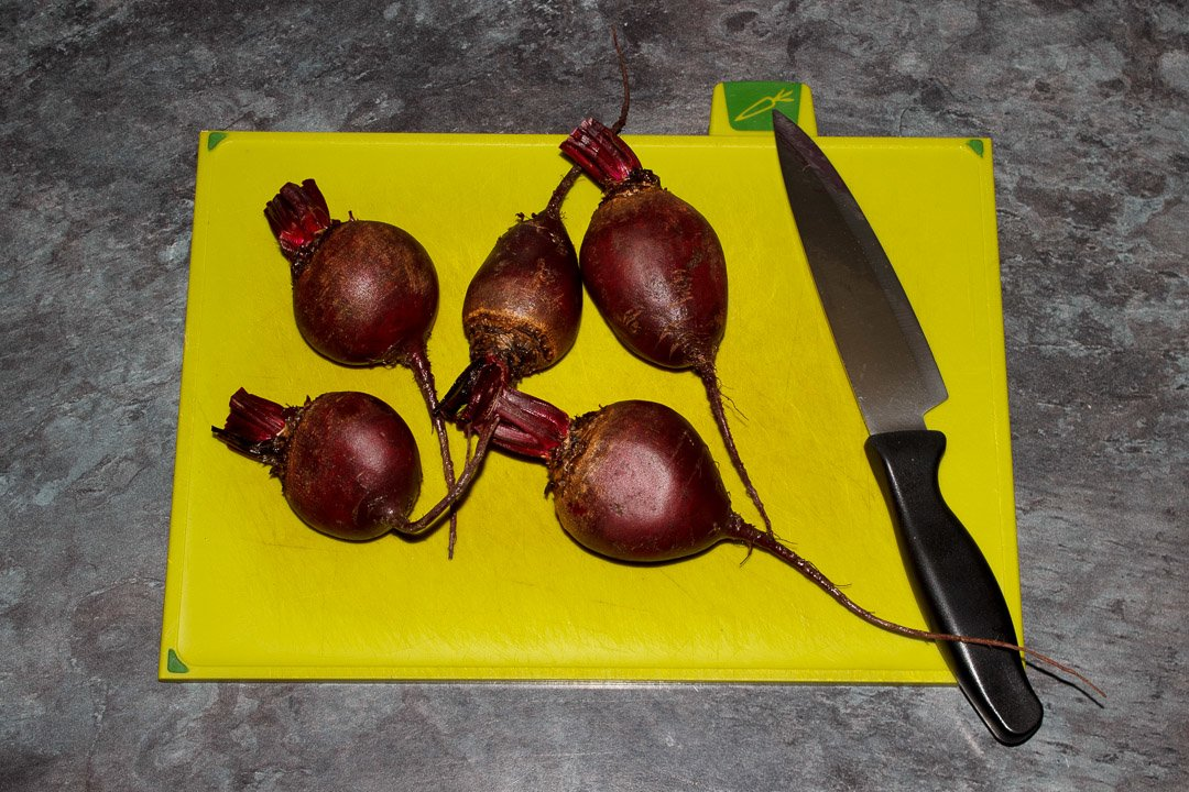 Washed whole beetroot with the stems trimmed on a chopping board with a knife