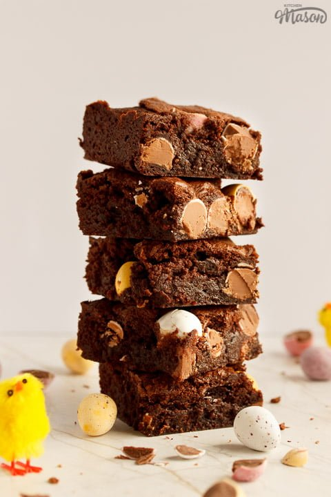 A stack of 5 Mini Egg brownies surrounded by broken Mini Eggs and Easter chicks
