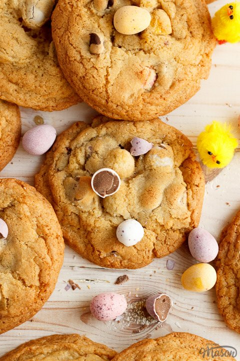 Mini Egg cookies in a pile on a worktop alongside scattered Mini Eggs and little yellow chicks