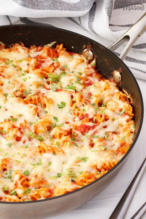 Tuna pasta bake in a large frying pan on a white table cloth with two silver forks