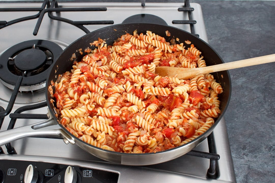 Tuna pasta bake in a large frying pan on a hob